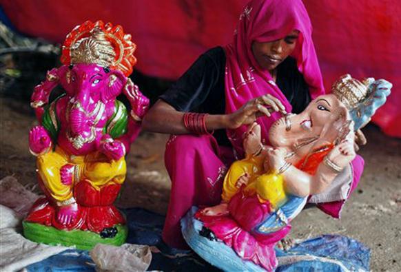 मुर्तीचे रंगकाम करताना महिला