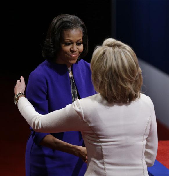 मिशेल ओबामा आणि अॅना रॉम्नी दोघी एकमेकांना शुभेच्छा देताना
