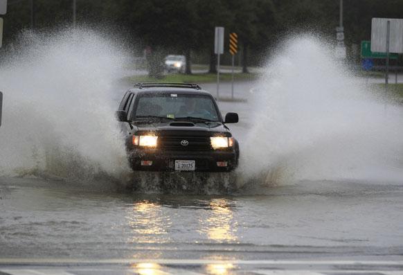 अमेरिकेतील नॉरफोक मार्गावर रस्तावर आलेल्या पाण्यातून वाट काढताना एक गाडी.