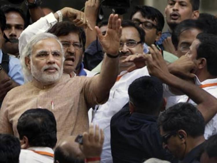 अहमदाबाद येथील निवडणुक रॅलीमध्ये कार्यकर्त्यांसोबत उतरलेले नरेंद्र मोदी