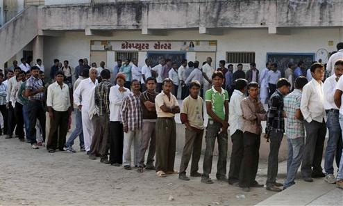 गुजरातमधील पहिल्या टप्प्याच्या मतदानावेळी बुथ बाहेर लागलेली रांग