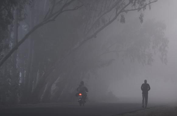 धुक्यातून मोटरबाईस्वार जाताना. हे दृश्य आहे जम्मूतील