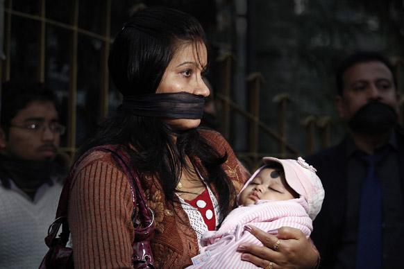 आपल्या तान्हुल्याला घेत तोंडावर पट्टी बांधून निषेध व्यक्त करताना गुवाहाटीतील एक महिला.