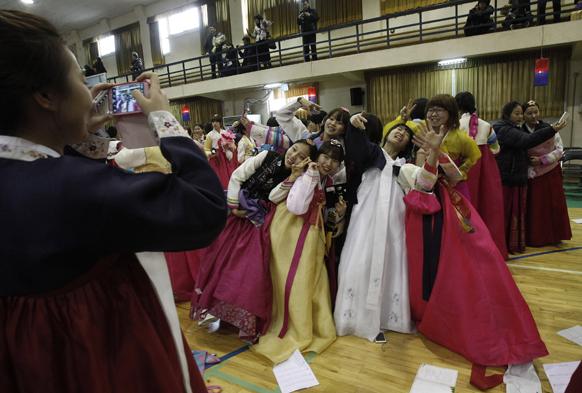 दक्षिण कोरियामध्ये पारंपरिक वेशभुषा केलेले शालेय विद्यार्थी आपल्या छबी कॅमेऱ्यात टिपन्यासाठी दिलेली पोझ.