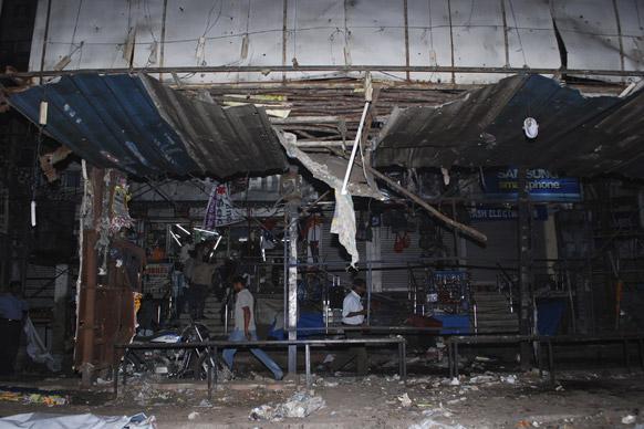 हैदराबाद स्फोटः उद्धवस्त बस स्टॉपजवळून जातांना नागरिक