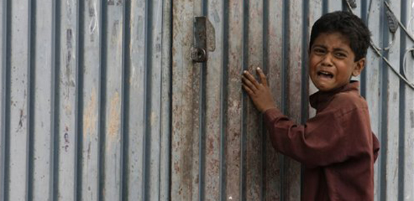 बॉम्बस्फोटाच्या धक्क्याने घाबरलेला एक पाकिस्तानी चिमुकला....
