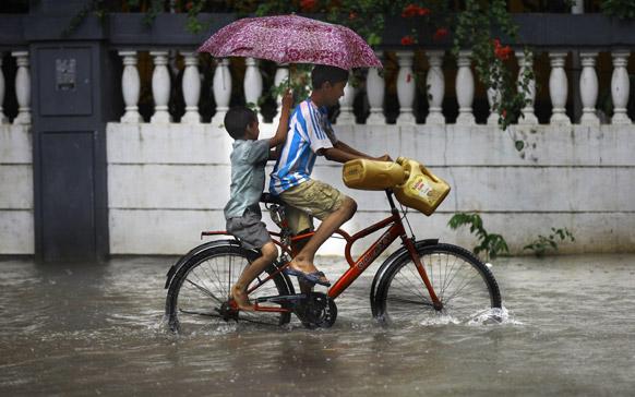 मुंबईत दोन दिवसांपूर्वी आलेल्या पावसामुळे सखल भागात पाणी साचले होते. या पाण्यातून सायकलवरून वाट काढताना मुले