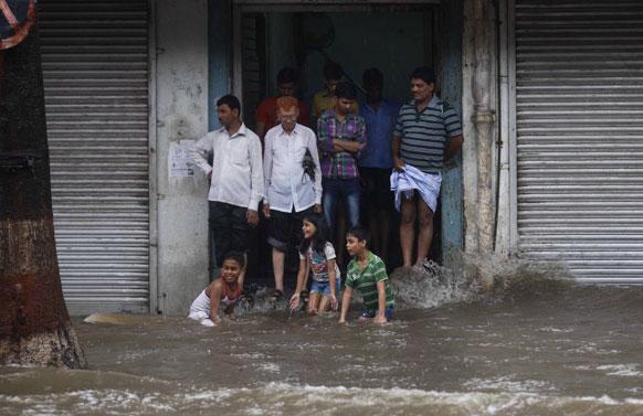 मुंबईत दोन दिवसांपूर्वी आलेल्या पावसामुळे सखल भागात पाणी साचले होते. या पाण्यात खेळताना मुले तर वयस्करांनी इमारतीचा आसरा घेतला होता.