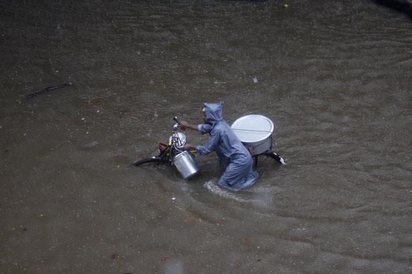 मुंबईत दोन दिवसांपूर्वी आलेल्या पावसामुळे सखल भागात पाणी साचले होते. या पाण्यातून वाट काढताना सायकल स्वार.