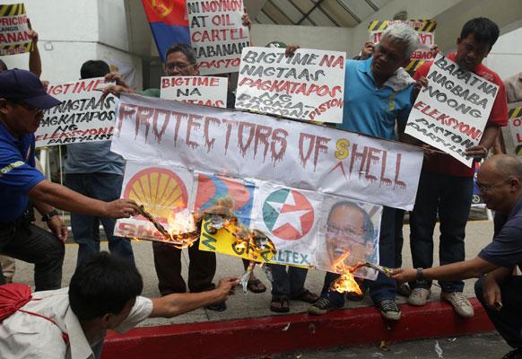 फिलिपिनो सदस्य तेल कंपन्यांचं स्लोगन जाळताना