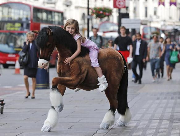 लंडनमध्ये  एका खेळण्याच्या दुकानात छोटी मुलगी घोड्यावर बसून एक सुंदर पोझ देताना