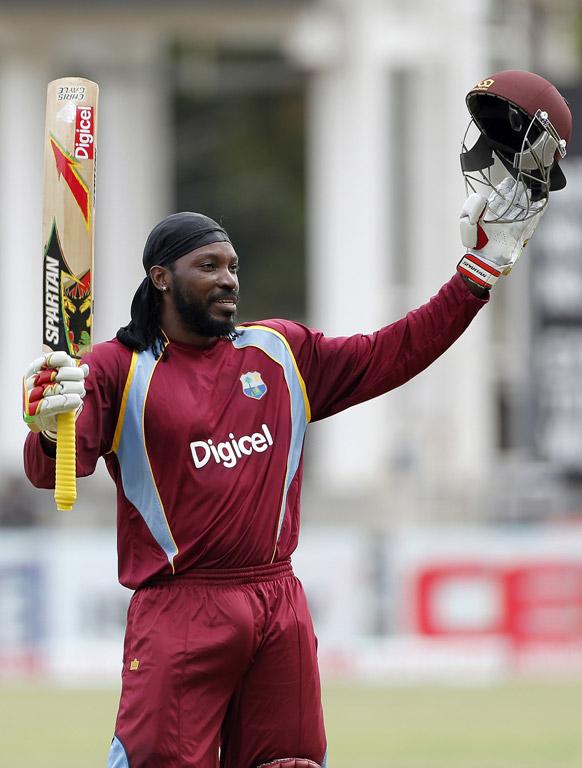 वेस्ट इंडिजचा फलंदाज ख्रिस गेल किंगस्टोन, जमेका मध्ये श्रीलंकेविरुद्ध तिरंगी मालिकेत राष्ट्र क्रिकेट मॅचमध्ये शतक पूर्ण केल्यावर हातात बॅट आणि हेलमेट घेऊन आनंद व्यक्त करताना