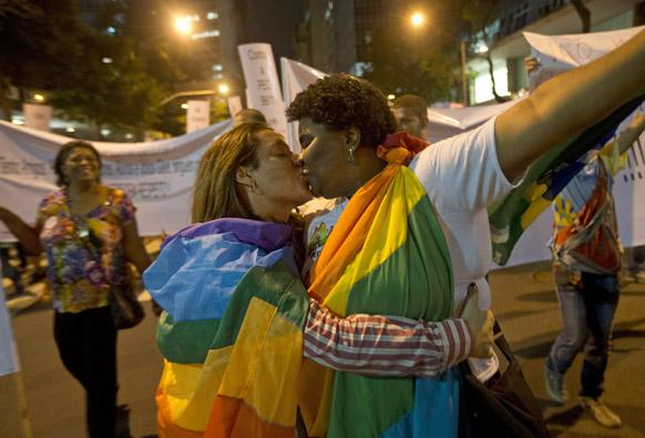 दोन समलिंगी झेंडा गुंडाळून होमो फोबियाचा निषेध करताना रियो दि जानेरो, ब्राझिलमध्ये