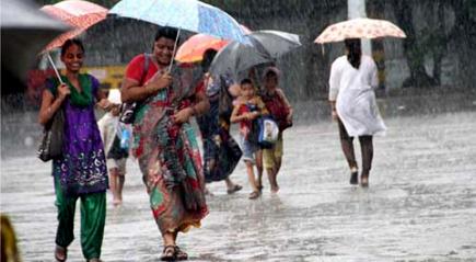 मुसळधार पाऊस कोसळत असल्याने पावसाचा सामना करताना महिला
