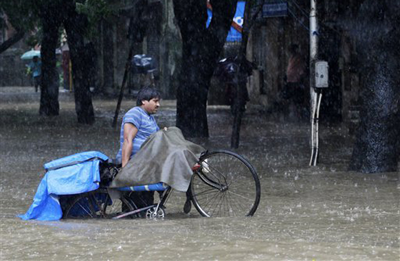 जोरदार पावसाने मुंबईत ठिकठिकाणी पाणी साचलेय. सायकलस्वार पाण्यातून रस्ता काढताना