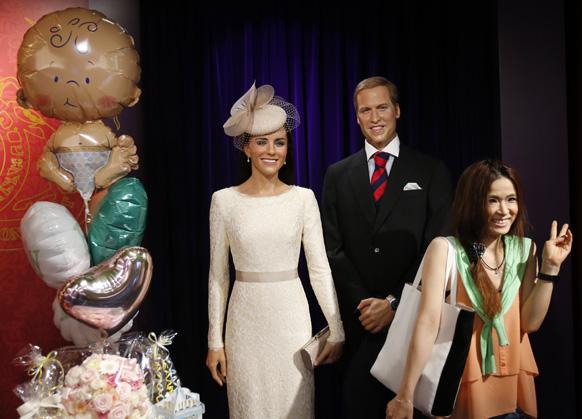 प्रिन्स विल्यम्स आणि त्यांची पत्नी केट मिडलटन यांच्या मेणाच्या पुतळ्यासमोर पर्यटक फोटो काढताना