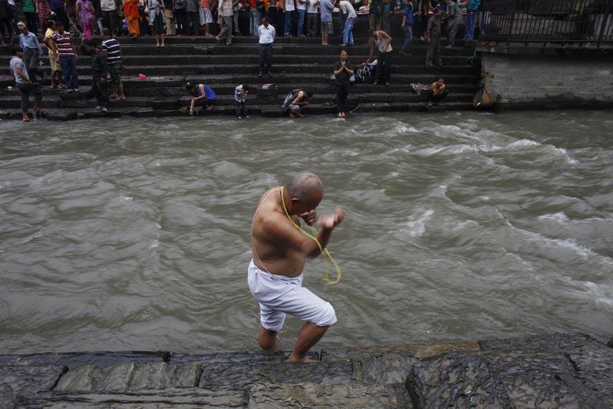 नेपाळमध्ये हिंदूंचा पवित्र धागा महोत्सव....एक नेपाळी हिंदू काठमांडू येथे पशुपती मंदिर जवळील बागमती नदी प्रार्थना करताना.