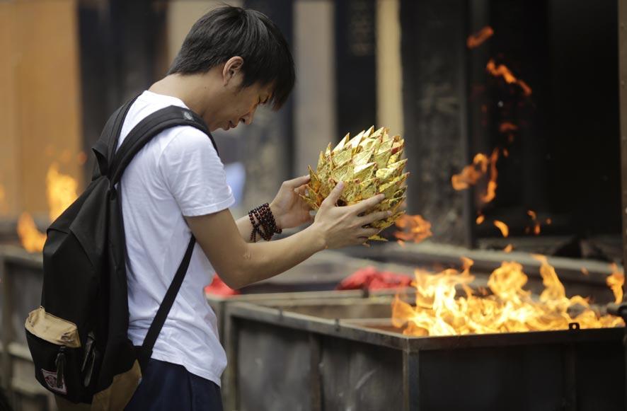 चीनमध्ये भूत महोत्सव...  पूर्वजांची पुजा करण्यासाठी हा महोत्सव आयोजित करण्यात येता. एका मंदिरात आलेली व्यक्ती.