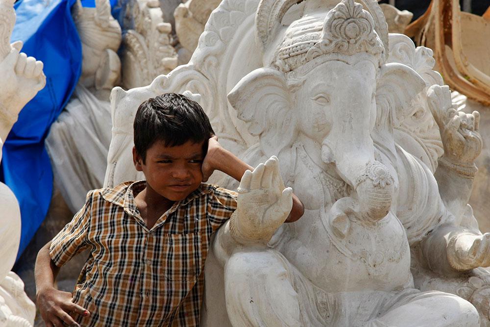 हैदराबाद येथे गणेश मूर्तीच्या कारखान्यात उभा असलेला मुलगा.