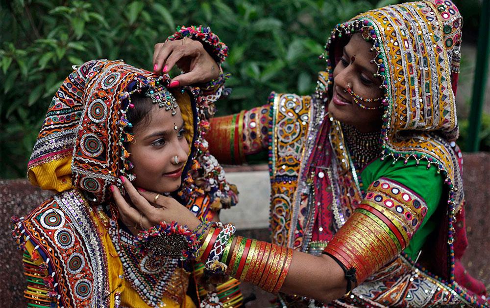 नवरात्री महोत्सव : अहमदाबाद येथे  गरबा नृत्यासाठी मुलीला सजवताना एक महिला.