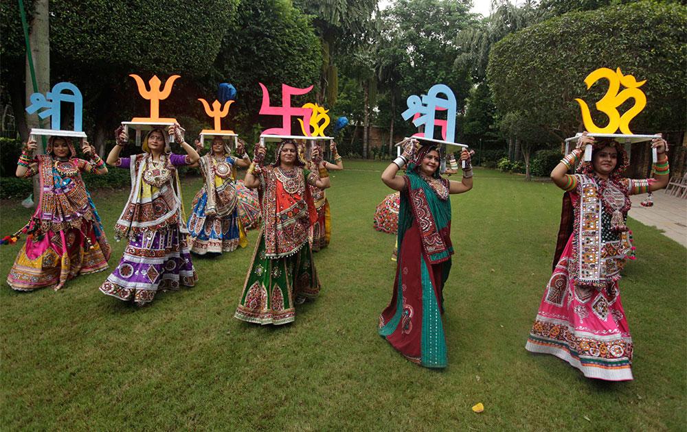 पारंपरिक वस्त्रं परिधान करून डोक्यावर हिंदू संस्कृतीतील शुभ चिन्हं घेतलेल्या महिला