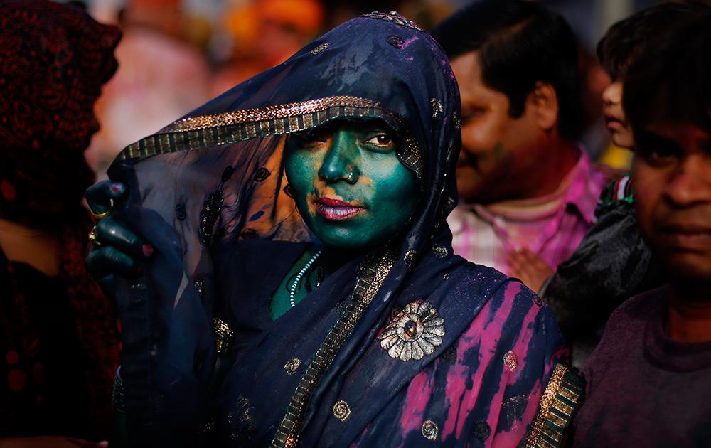 भगवान श्रीकृष्णाच्या नंदगाव इथं साजऱ्या होणाऱ्या प्रसिद्ध कृष्ण मंदिरात लाठमार होळी उत्सव साजरा करणारी, रंगांनी नाहून निघालेली ही महिला...