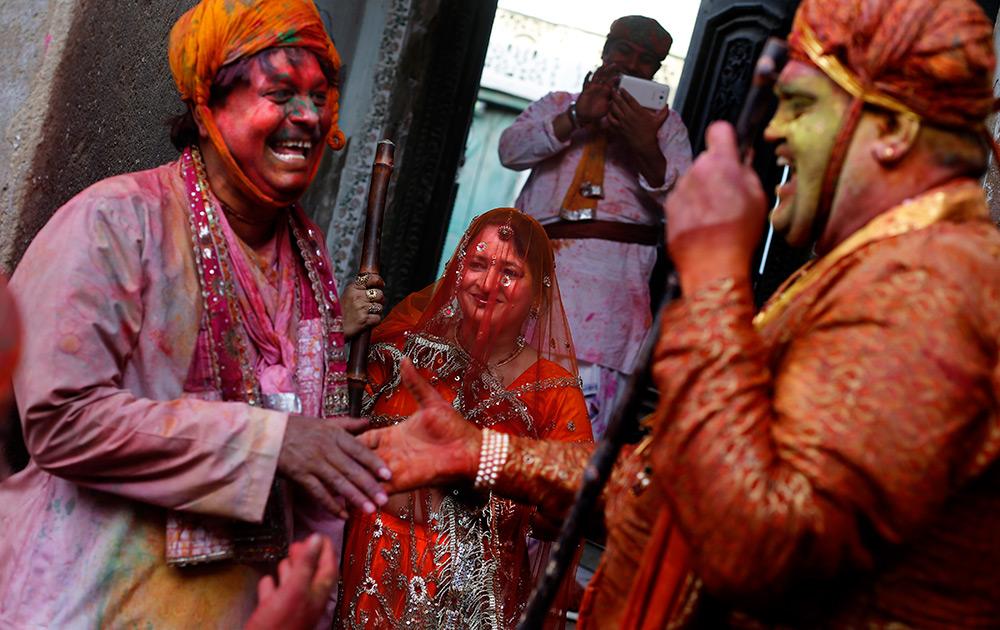 पारंपरिक लाठीमार होळीसाठी हातात काठी घेऊन बरसानाची महिला आणि श्रीकृष्णाच्या नंदगावाचा नागरिकासोबत... होळी उत्सव साजरा करतांना...