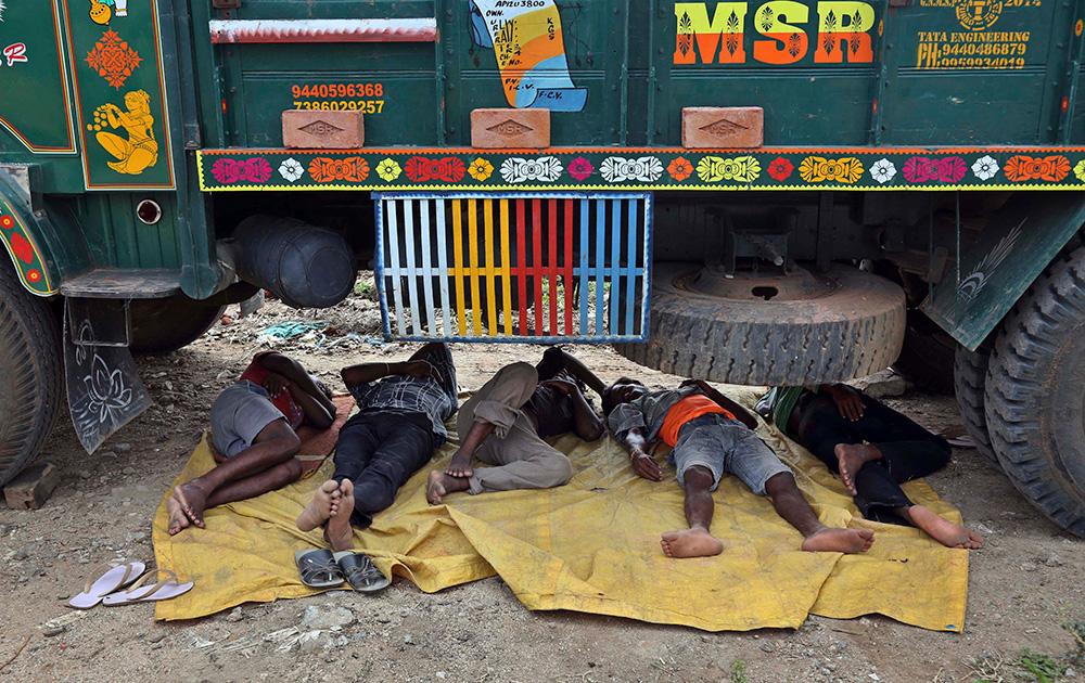 हैदराबादमध्ये गर्मीनं हैराण झालेले मजूर ट्रक खाली झोपले