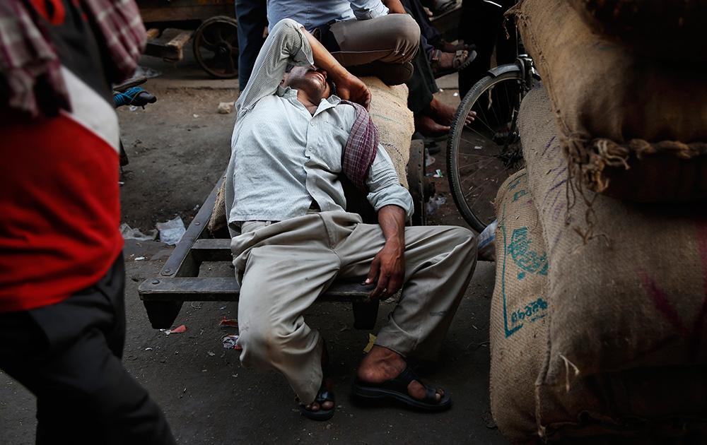 दिल्लीतल्या बाजारात कामातून थो़डा वेळ काढत झोप काढतांना मजूर...