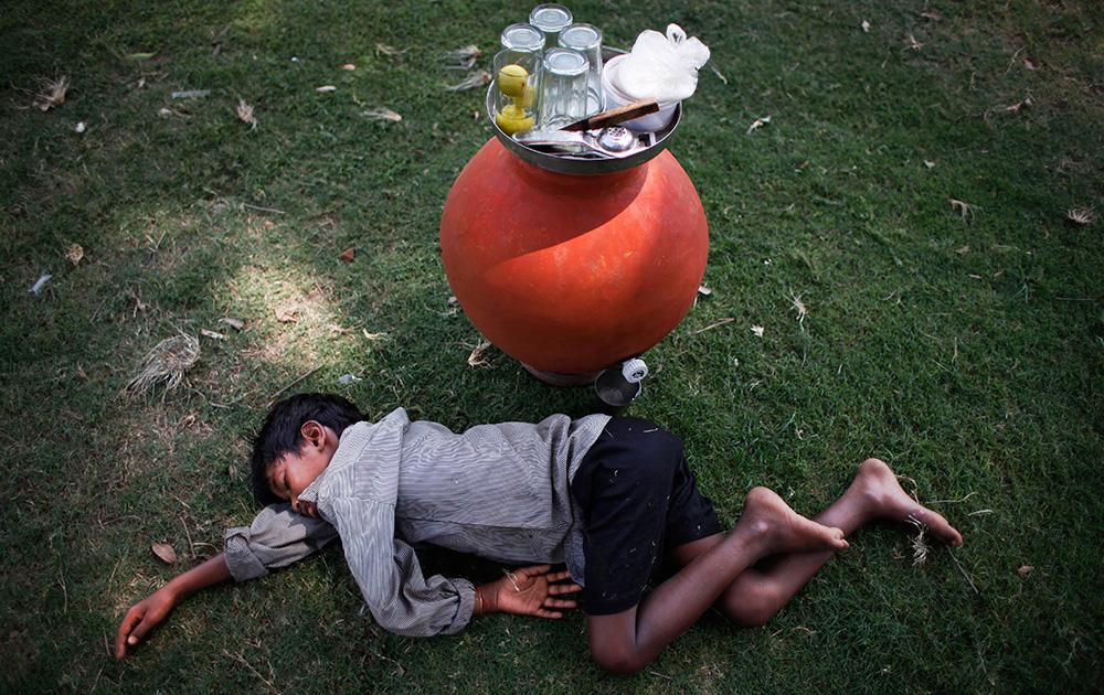 नवी दिल्लीच्या पार्कमध्ये निंबूपाणी विकणारा हा चिमुकला उष्म्यानं हैराण होऊन तिथंच गार गवतावर झोपला...