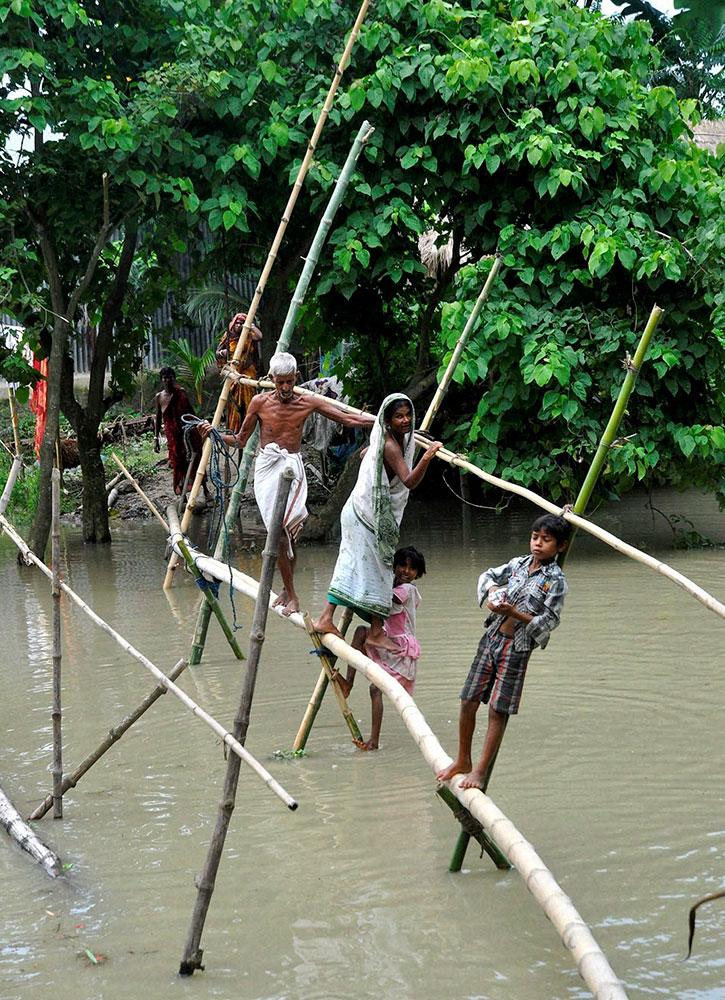आसाममध्ये पूरग्रस्त गावात बाबूंच्या आधाराने सुरक्षित ठिकाणी जातांना गावकरी
