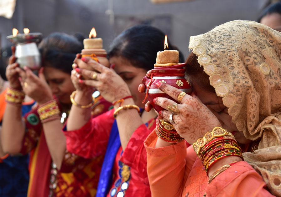 Women perform rituals related to Karva Chauth in Bikaner.