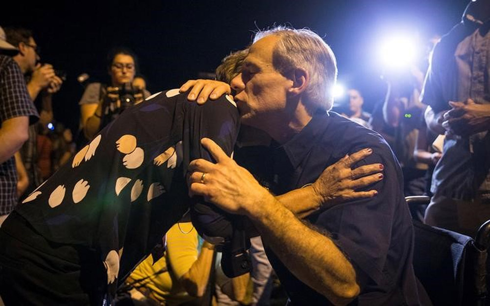 Texas Governor Greg Abbott embraces a woman at a vigil following a mass shooting at the First Baptist Church in Sutherland Springs.
