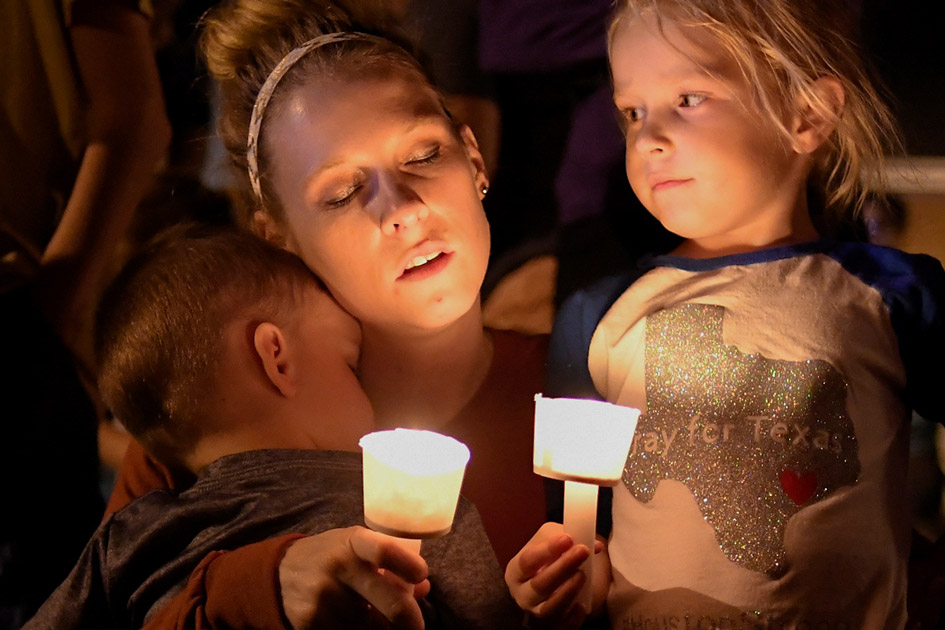 A woman and her children take part in a vigil for victims of a mass shooting in Sutherland Springs, Texas.