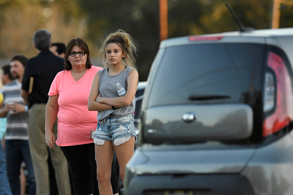 Local residents gather outside the Sutherland Springs Community Building after a mass shooting in Texas.