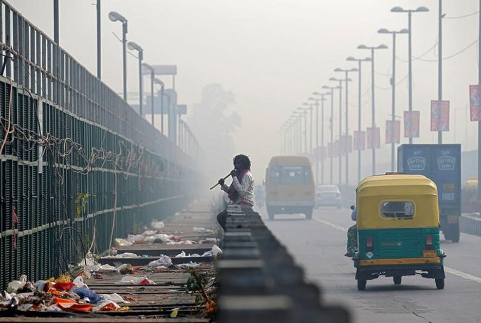 Man chews sugarcane on a bridge during smoggy morning in New Delhi.