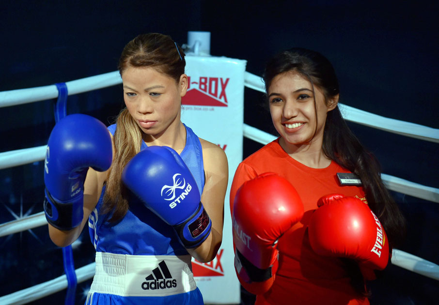 A volunteer poses with the wax figure of Boxing legend Mary Kom which was displayed at Madame Tussauds Wax Museum, during a press preview in New Delhi.