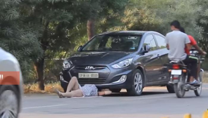 एक सुंदर 'तरुणी'  रस्त्यावर कारच्या खाली! VIDEO पाहा पुढे काय झाले?